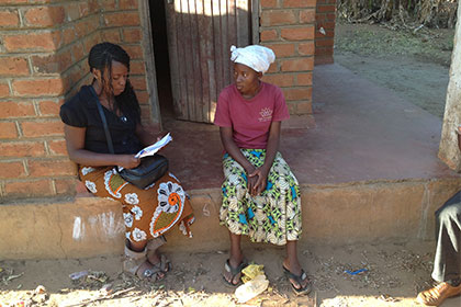 female worker gives survey to local mother